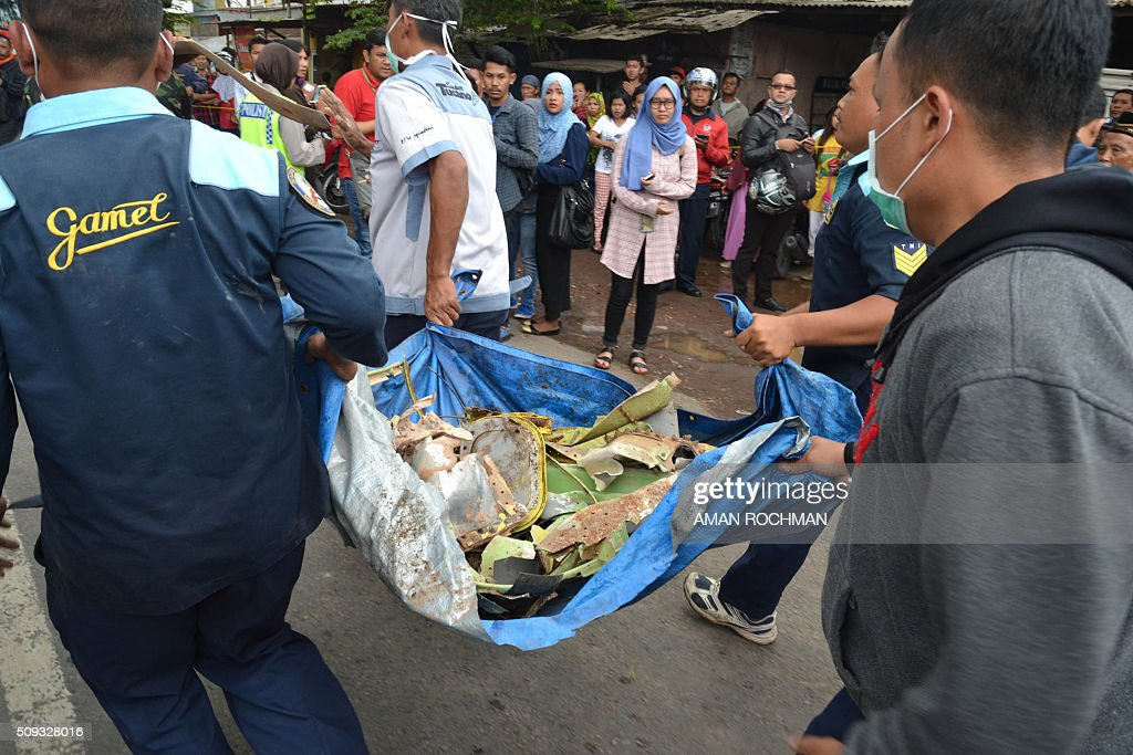 Indonesian officials carry wreckage from a military plane after it crashed while on a test flight from the local air force base into a house in a densely populated area in Malang on February 10, 2016. The Super Tucano turboprop came down shortly after taking off from Abdul Rachman Saleh air force base at Malang in East Java, killing the pilot and two people in the building, an air force official said. AFP PHOTO / AMAN ROCHMAN / AFP / AMAN ROCHMAN