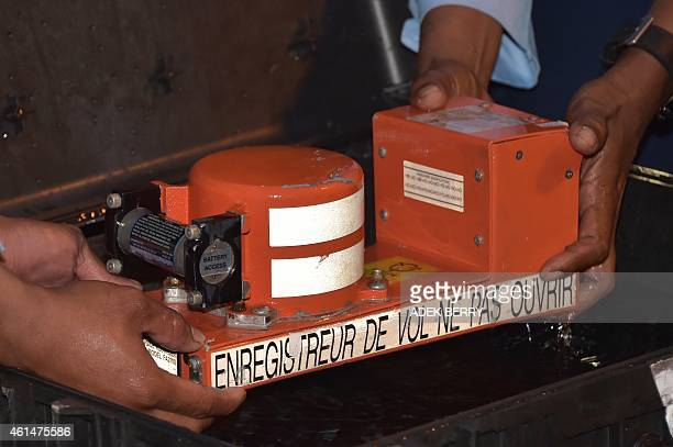 Indonesian officials remove the cockpit voice recorder from AirAsia flight QZ8501 upon its arrival in Pangkalan Bun on January 13 2015 Indonesian...