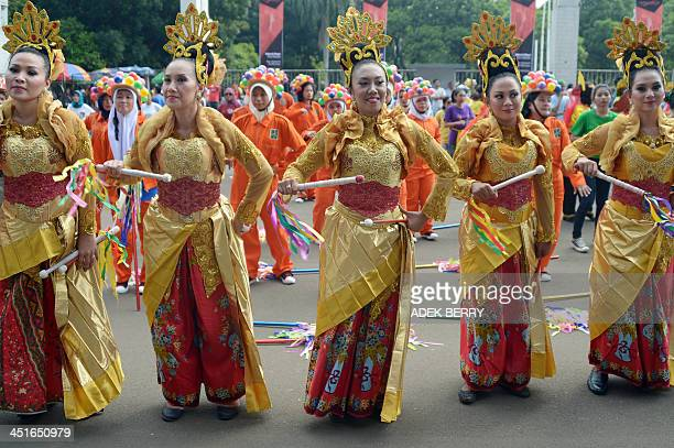 Indonesian participants dance during 'Indonesia Menari' an Indonesian dance event in Jakarta on November 24 2013 The event is held to encourage...