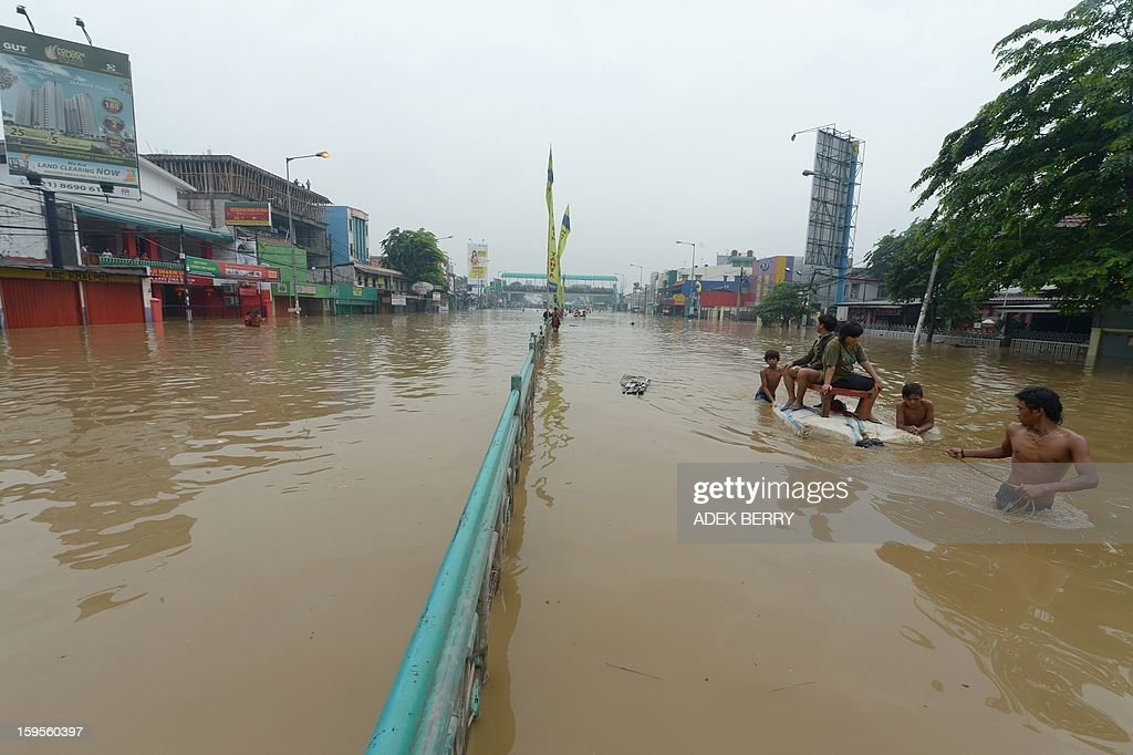 Indonesian people ride a cart pulled by men as they wade through a flooded street in Jakarta on January 16, 2013. Floodwaters have inundated 52 subdistricts in Jakarta, claiming one life and displacing some 6,000 residents, according to the National Disaster Mitigation Agency (BNPB).