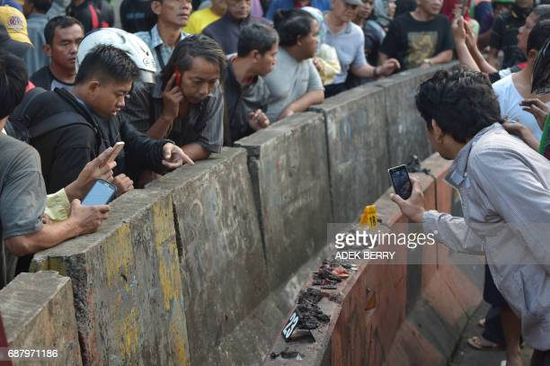 TOPSHOT Indonesian people stand next to human body parts at a scene where two bombers launched an attack in Jakarta on May 25 2017 A suicide bombing...