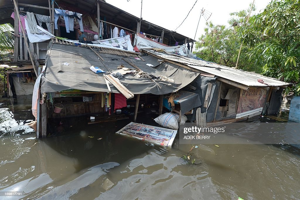 Indonesian people stay at their houses surounded by floodwaters in Jakarta on January 21, 2013. Companies and consumers have started to calculate damages and losses from the widespread floods that hit Jakarta last week, claiming at least 15 lives, displacing thousands from their homes and afflicting capital residents with water-borne illnesses, a local newspaper reported. AFP PHOTO / ADEK BERRY