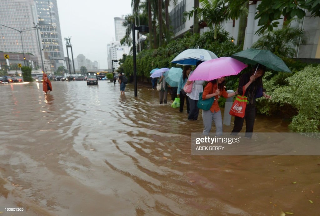 Indonesian people wade through a flooded main street in Jakarta on February 6, 2013. Heavy downpour caused floods on the streets even though Indonesian authorities used generators and cloud-seeding measures to defuse and push away rain-laden clouds. The rainy season is expected to last until March.