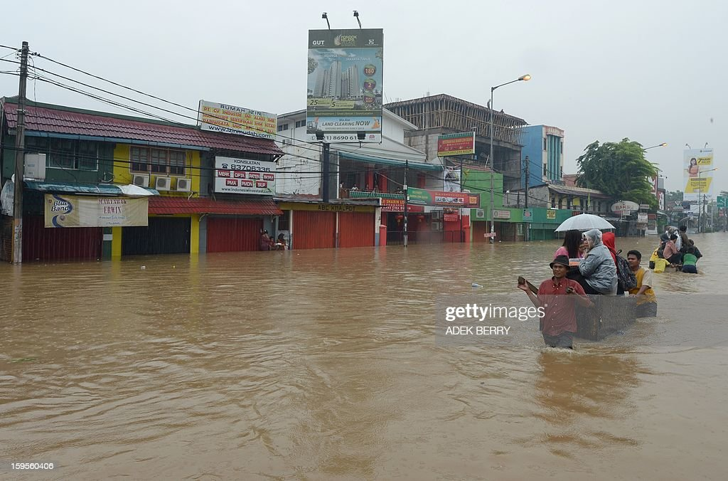 Indonesian people wade through a flooded street in Jakarta on January 16, 2013. Floodwaters have inundated 52 subdistricts in Jakarta, claiming one life and displacing some 6,000 residents, according to the National Disaster Mitigation Agency (BNPB).