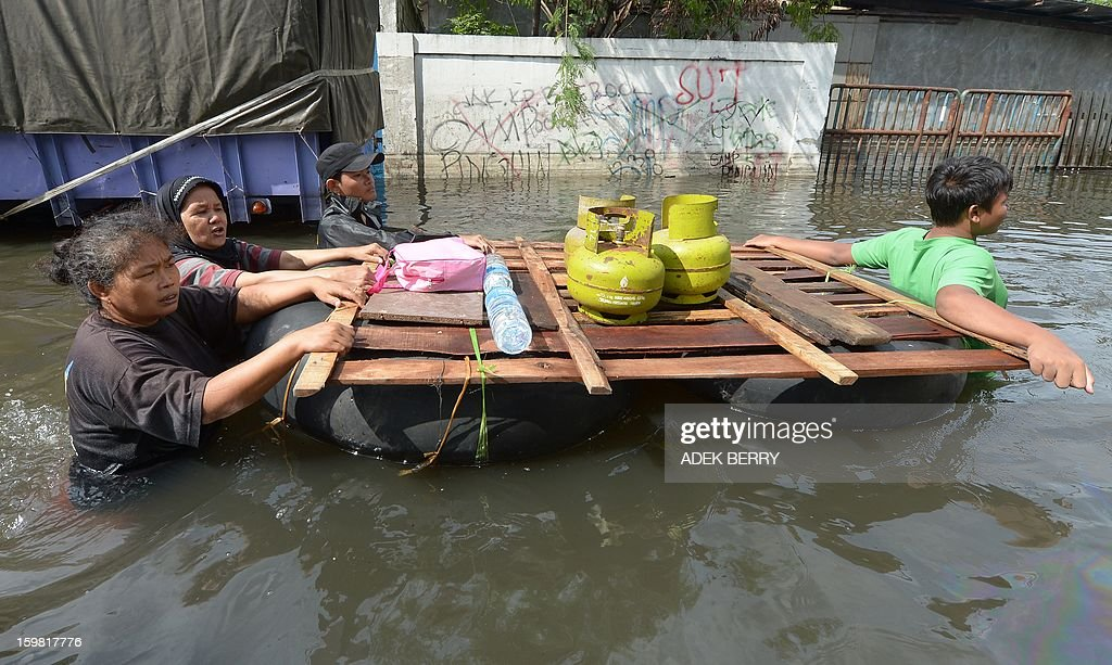 Indonesian people wade through a flooded street to get free cooking gas in Jakarta on January 21, 2013. Companies and consumers have started to calculate damages and losses from the widespread floods that hit Jakarta last week, claiming at least 15 lives, displacing thousands from their homes and afflicting capital residents with water-borne illnesses, a local newspaper reported.