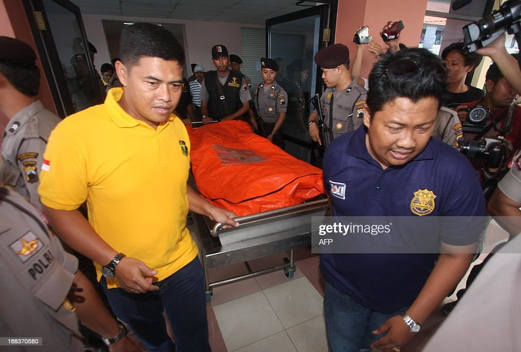 Indonesian plain clothes police carry suspected terrorist Abu Roban's dead body out from the autopsy room of a police hospital in Semarang, Central Java, on May 9, 2013, after a raid at Roban's hiding place in Kendal, Central Java, on May 8. Thirteen suspects were captured alive as an elite police unit swooped on houses across the country's main island of Java, in the biggest counter-terrorism operation in Indonesia for months. Indonesian police have shot dead seven terror suspects in raids over the past two days, including several with alleged links to a plot to bomb the Myanmar embassy, officials said. AFP PHOTO / Setiawan