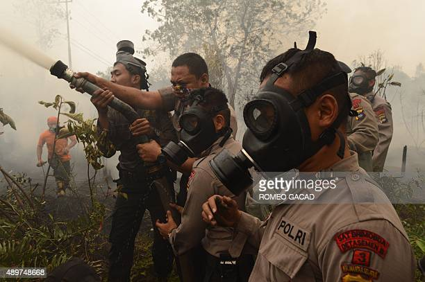 Indonesian police and firefighters extinguish a fire on burning peat land in the district of Kapuas in the Central Kalimantan province on Borneo...