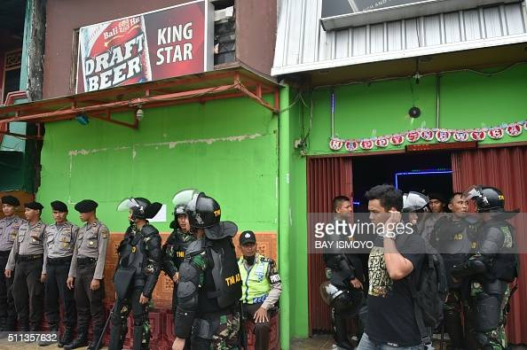 Indonesian police and military personnel weep watch outside a cafe during a raid at the Kalijodo redlight district in Jakarta on February 20 2016 The...