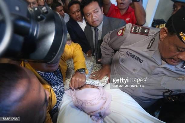 Indonesian police and relatives escort parliamentary speaker Setya Novanto as he is transferred by stretcher to another hospital in Jakarta on...
