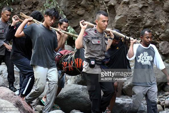 Indonesian police and villagers carry the body of a flash flood victim in Sibolangit North Sumatra on May 16 2016 At least eight people were killed...