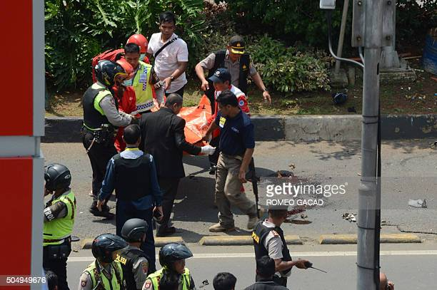 Indonesian police carry a body bag containing one of the bodies recovered outside a traffic police outpost after a series of explosions hit central...