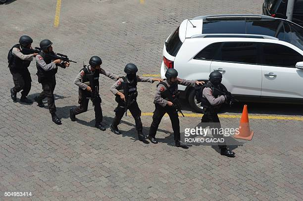 Indonesian police commandos arrive near a damaged Starbucks coffee shop after a series of explosions hit central Jakarta on January 14 2016 An...