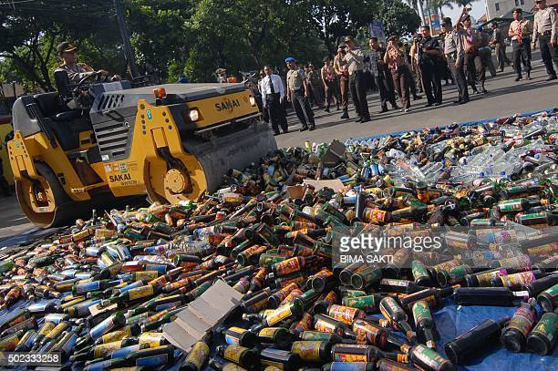 Indonesian police destroy bottles of alcoholic drinks at a police station in Tangerang on December 23 2015 Indonesian police destroyed bottles of...