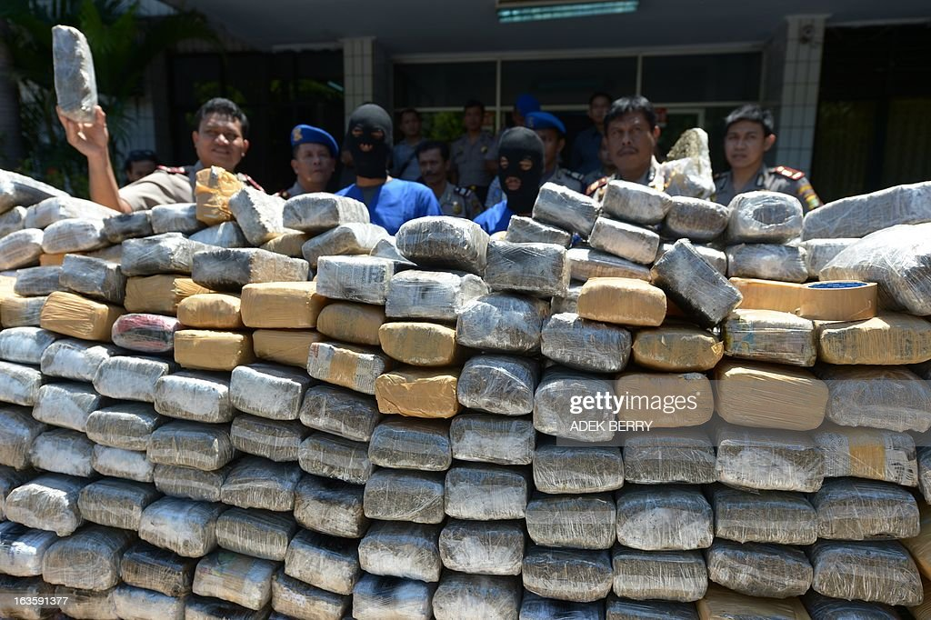 Indonesian police display one tonne of marijuana and two suspects (C) seized during a recent operation in Jakarta on March 13, 2013. Indonesian police arrested two Indonesian suspects on March 11 in Cianjur, West Java and seized about one tonne of marijuana valued at 237,000 USD.