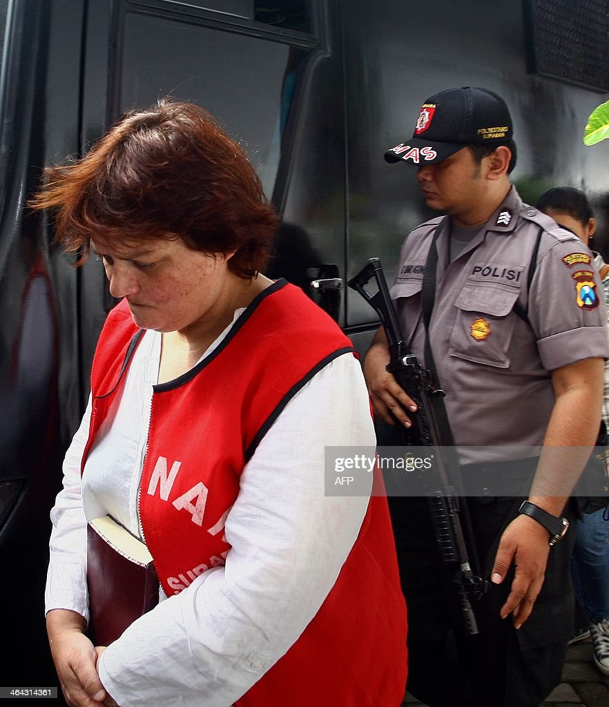 Indonesian police escort Andrea Waldeck to her trial at a court in Surabaya on January 22, 2014. The British woman was jailed for 14 years on January 22 but escaped the death penalty after admitting that she smuggled crystal methamphetamine into Indonesia from China. AFP PHOTO / JUNI KRISWANTO