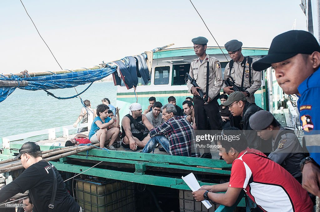 Indonesian police guard an asylum seeker boat on May 12, 2013 in Bali, Indonesia. Indonesian police have intercepted an asylum seeker boat harboured in Bali that was believed to be heading to Australia. 80 to 100 people of Middle Eastern origin where found in the hull of a wooden boat on Benoa Harbour.