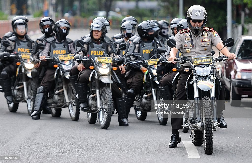 Indonesian Police heavily guard a protest demanding higher wages on May Day on May 1, 2014 in Surabaya, Indonesia. Protesters across Indonesia have organised rallies to demand higher wages, as Indonesia recognises its first national labour day holiday.