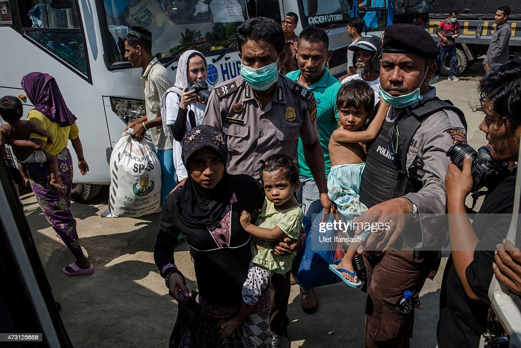Indonesian police help Rohingya migrants to board on a bus as relocated to their new temporary shelter on May 13 2015 in Lhoksukon Aceh province...