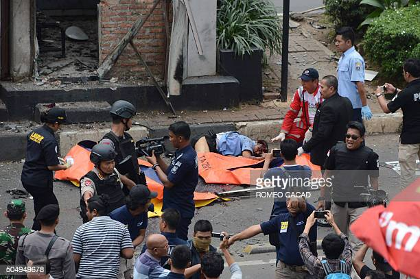 TOPSHOT Indonesian police place body bags next to victims outside a traffic police outpost after a series of explosions hit central Jakarta on...