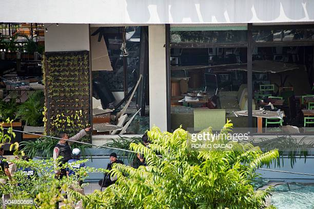 Indonesian police secure the area in front of a damaged Starbucks coffee shop after a series of explosions hit central Jakarta on January 14 2016...
