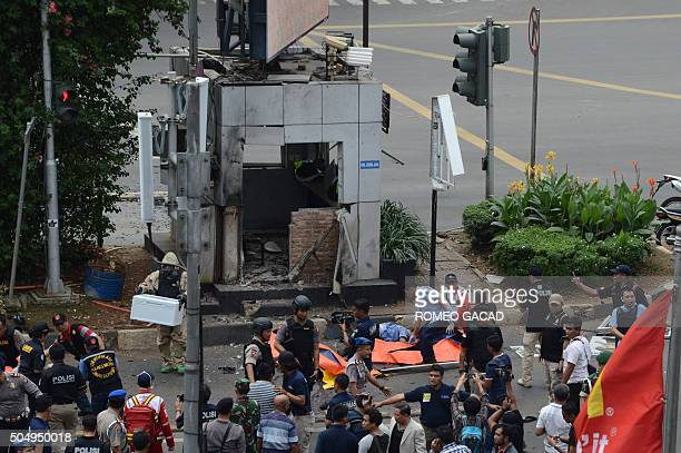 Indonesian police secure the scene next to victims outside a traffic police outpost after a series of explosions hit central Jakarta on January 14...
