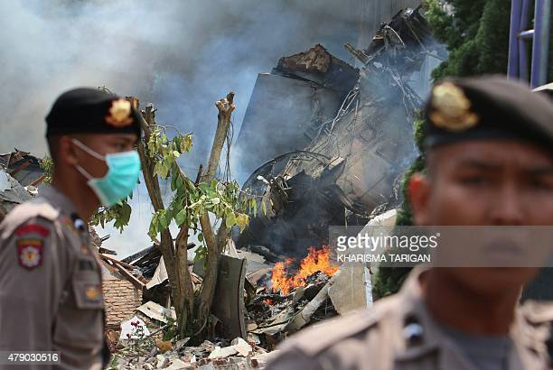 Indonesian police secure the scene where an Indonesian military C130 Hercules crashed into a residential area in Medan on June 30 2015 An Indonesian...