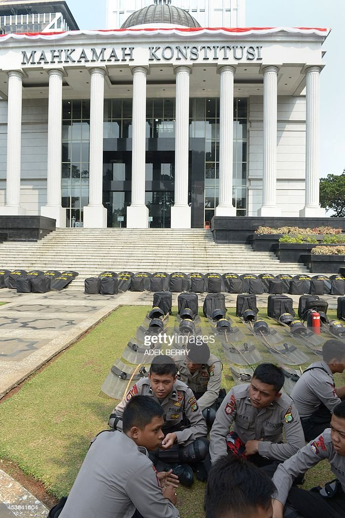 Indonesian police sit outside the Constitutional Court in Jakarta on August 20, 2014, as authorities increase security ahead of the announcement on August 21 of its decision about the presidential election dispute. Indonesian ex-general Prabowo Subianto angrily claimed widespread cheating cost him victory in the country's presidential election at the start of legal challenge to the results on August 6. Prabowo, a controversial former military figure with roots in the era of dictator Suharto, also declared victory at the July 9 presidential election, but official results two weeks later confirmed Joko Widodo won a decisive victory.