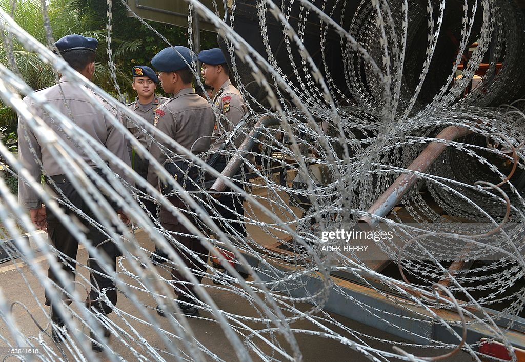 Indonesian police stand next to barbed wire outside the Constitutional Court in Jakarta on August 20, 2014, as authorities increase security ahead of the announcement on August 21 of its decision about the presidential election dispute. Indonesian ex-general Prabowo Subianto angrily claimed widespread cheating cost him victory in the country's presidential election at the start of legal challenge to the results on August 6. Prabowo, a controversial former military figure with roots in the era of dictator Suharto, also declared victory at the July 9 presidential election, but official results two weeks later confirmed Joko Widodo won a decisive victory. AFP PHOTO / ADEK BERRY