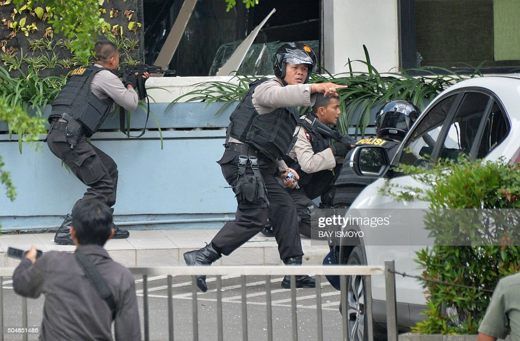 Indonesian police take position and aim their weapons as they pursue suspects outside a cafe after a series of blasts hit the Indonesia capital...