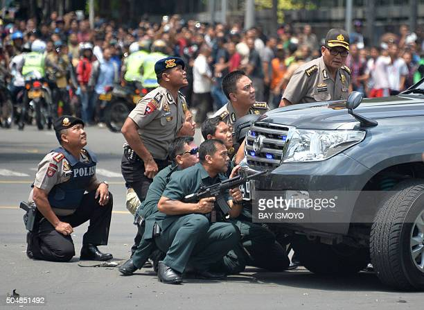 TOPSHOT Indonesian police take position behind a vehicle as they pursue suspects after a series of blasts hit the Indonesia capital Jakarta on...
