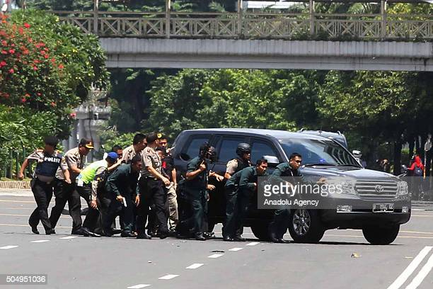 Indonesian police take position behind a vehicle as they pursue suspects after a series of blasts hit the Indonesia capital Jakarta on January 14...