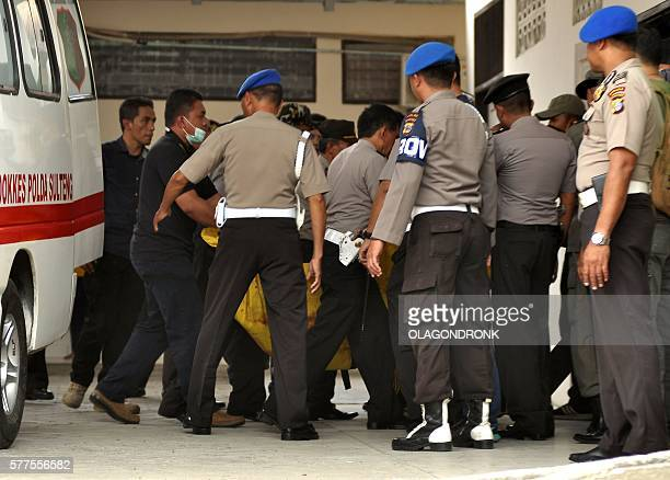 Indonesian police transfer a body bag from an ambulance at local hospital in Palu Central Sulawesi province on July 19 after a firefight between...