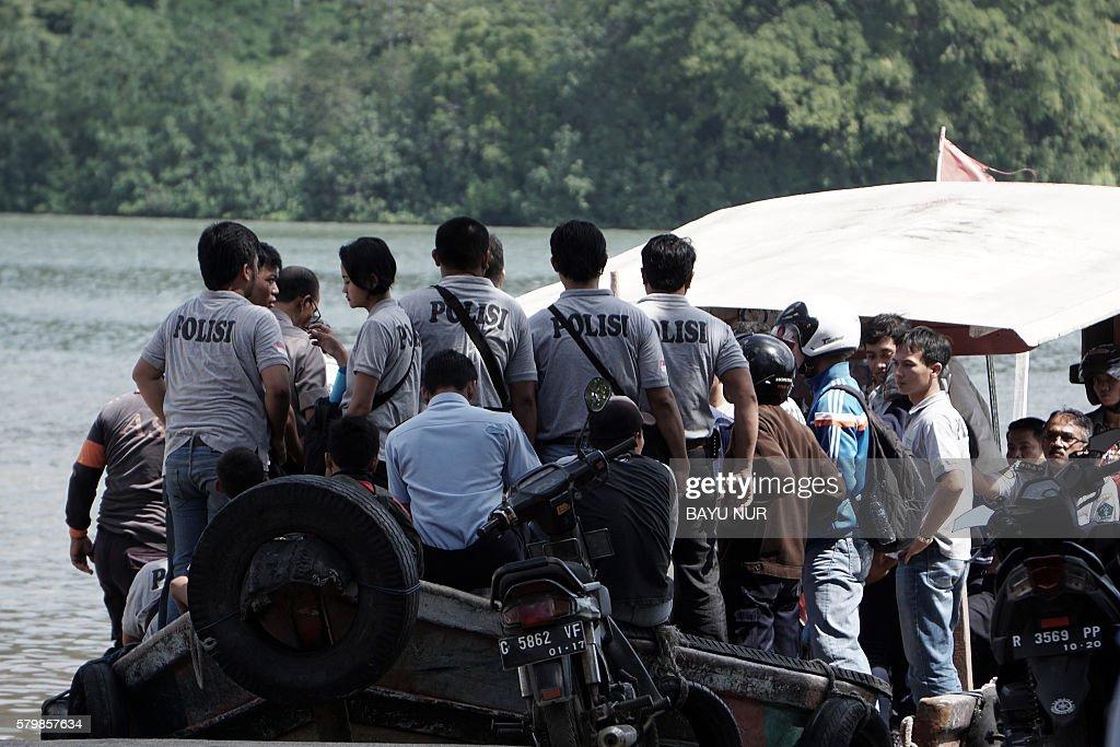 Indonesian policemen and residents of Nusakambangan take a boat to cross to Nusakambangan island at the Cilacap port the only gate to Indonesia's...