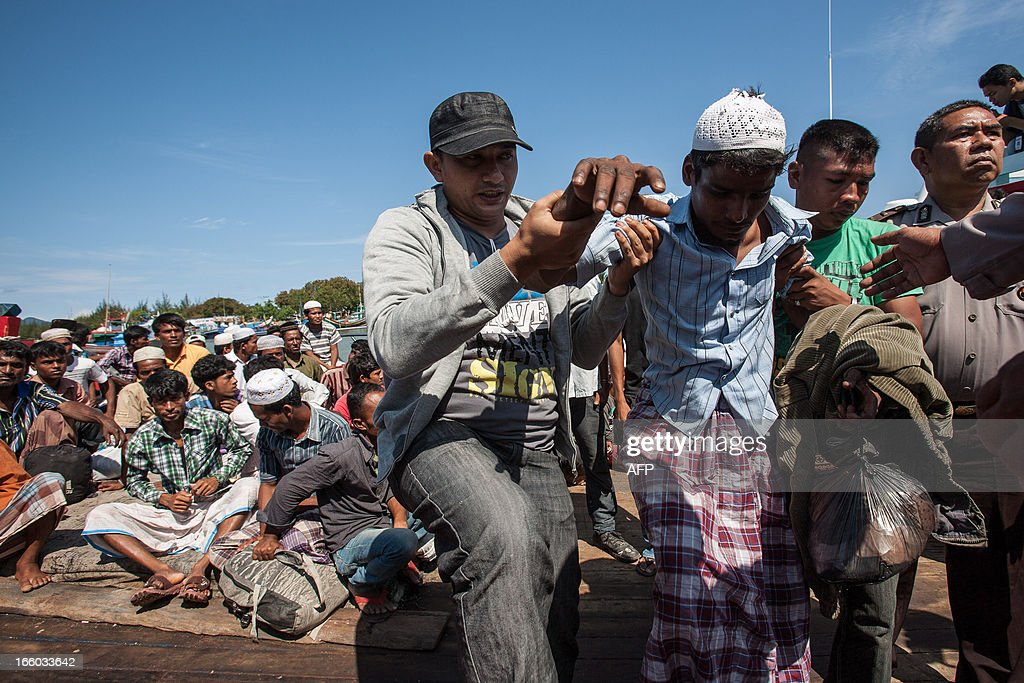 Indonesian policemen help a Rohingya Muslim from Myanmar in Banda Aceh on April 8, 2013, after they were stranded on the remote island of Pulo Aceh. Indonesian police on April 7 detained 80 Rohingya Muslims from Myanmar on a remote island off Sumatra after they had got lost attempting to reach Malaysia, an official said. It was the latest boatload of Rohingya to arrive on the shores of Indonesia, as thousands flee Myanmar after tensions between Muslims and Buddhists exploded in their home state of Rakhine last year.