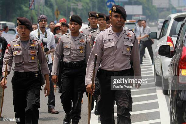 Indonesian policemen patrol after clashes between taxi drivers during a protest rally to demand the government to prohibit ridehailing apps