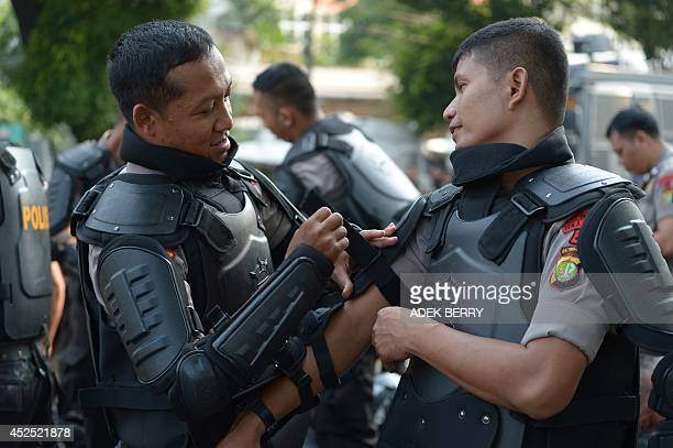 Indonesian policemen put on their gear as Indonesia's General Elections Commission continued the national tabulation in Jakarta on July 22 2014 The...