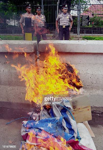 Indonesian policemen stand against a burning effigy of US President George W Bush and the US flag in front of the US embassy in Jakarta 15 February...