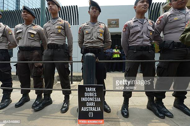 Indonesian policemen stand guard next to a banner that reads 'Withdraw Indonesian ambassador to Australia back to Jakarta' during a protest against...