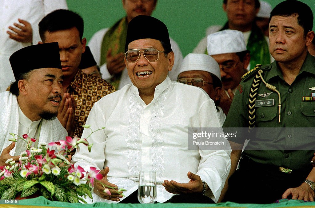 Indonesian President Abdurrahman Wahid laughs with officials as he participates in a mass prayer rally April 29, 2001 in Jakarta. The embattled Muslim cleric faces a parliamentary censure on April 30, a step towards his possible removal from office over a series of financial scandals.