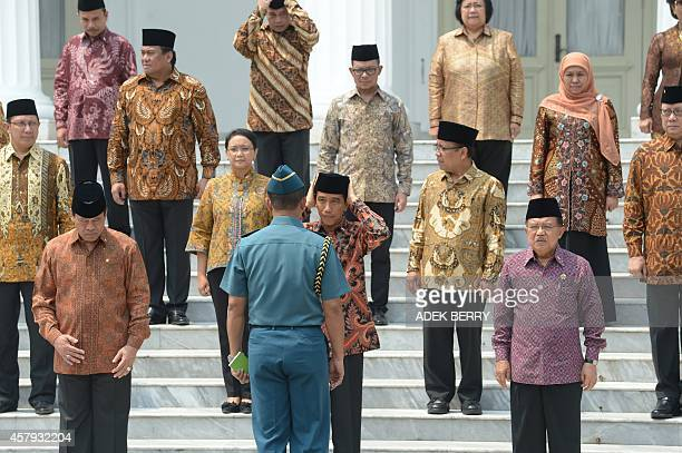 Indonesian President Joko Widodo adjusts his Muslim cap next to Vice President Jusuf Kalla Coordinating Minister for Political Legal and security...