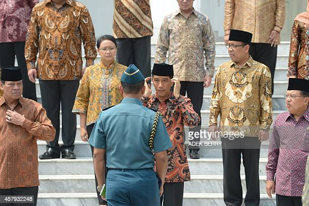 Indonesian President Joko Widodo adjusts his Muslim cap with his adjutant next to Vice President Jusuf Kalla and Coordinating Minister for Political...