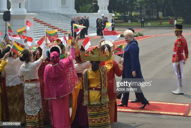 Indonesian President Joko Widodo and Lithuanian President Dalia Grybauskaite review Indonesian schoolchidren during a visit at the presidential...