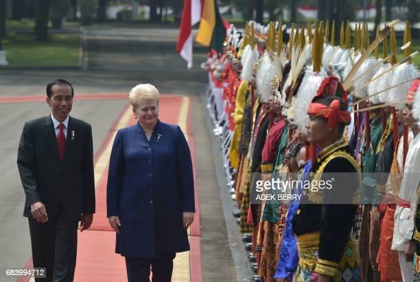 Indonesian President Joko Widodo and Lithuanian President Dalia Grybauskaite review Indonesian honour guards during a visit at the presidential...