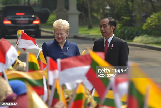 Indonesian President Joko Widodo and Lithuanian President Dalia Grybauskaite stand next to Indonesian school chidlren during a visit at the...