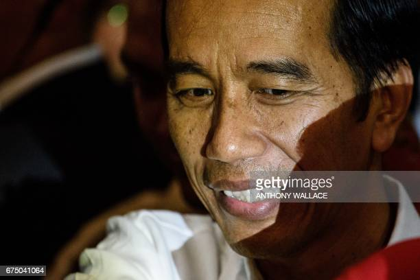 Indonesian President Joko Widodo looks on as he meets workers from Indonesia at an event during his visit to Hong Kong on April 30 2017 / AFP PHOTO /...