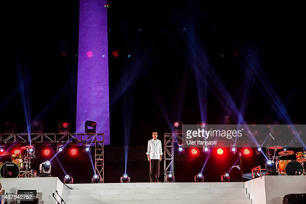 Indonesian President Joko Widodo stands on stage during the people celebration know as 'Pesta Rakyat' at National Museum on October 20 2014 in...