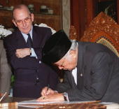 Indonesian President Suharto signs a new letter of agreement as International Monetary Fund DirectorGeneral Michel Camdessus at Suharto's residence...