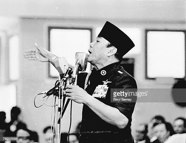 Indonesian President Sukarno dressed in a military uniform speaks from behind an array of microphones shortly after a series of attempted coups late...
