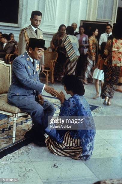 Indonesian President Sukarno extends his hand to a woman who kneels before him in formal greeting 1960s