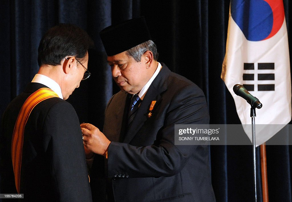 Indonesian President Susilo Bambang Yudhoyono (R) presents a medal award to South Korean President Lee Myung-bak (C) after their bilateral meeting at the Bali Democracy Forum (BDF) in Nusa Dua on Indonesia's resort island of Bali on November 8, 2012. The fifth Bali Democracy Forum has attracted record numbers of heads of state and government, including Australian Prime Minister Julia Gillard, Afghan President Hamid Karzai and South Korean President Lee Myung-Bak.